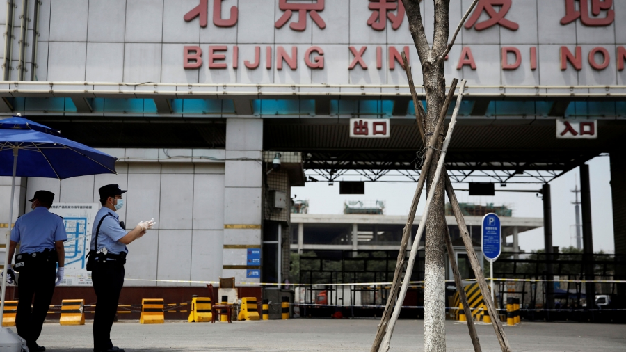 Two police officers are shown wearing protective face masks with the empty entrance to a food market in the background.