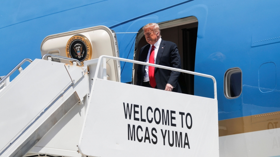 """US President Donald Trump is shown exiting the blue-painted Air Force  One on a white platform with the words, """"Welcome to MCAS Yuma"""" painted on the side."""
