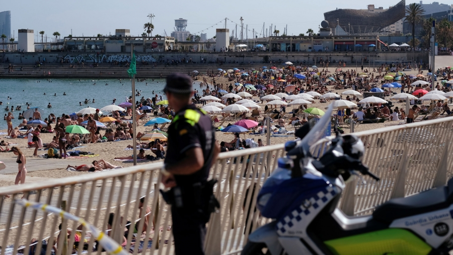 A police officer is shown in the nearground in soft focus with hundreds of beachgoers line the coast with umbrellas.