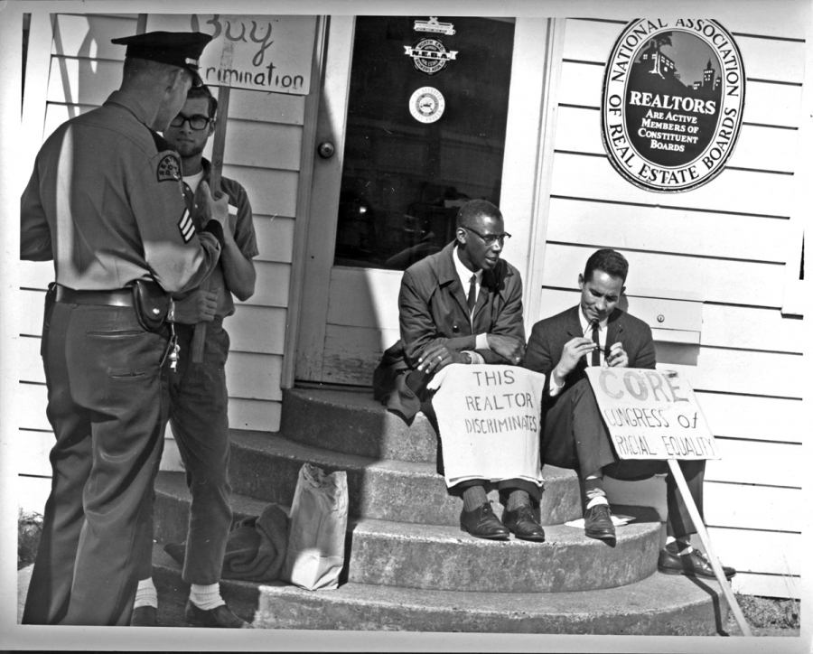 Two black men sit on steps with two white police offers standing by them.