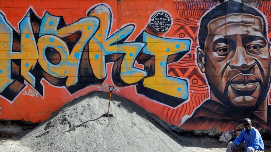 A man sits under a graffiti depicting African American man George Floyd, who was killed by a police officer in Minneapolis, in Kibera, Nairobi, Kenya.