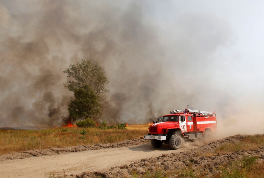 A red fire truck is shown driving across the frame with smoke and fire in the background.