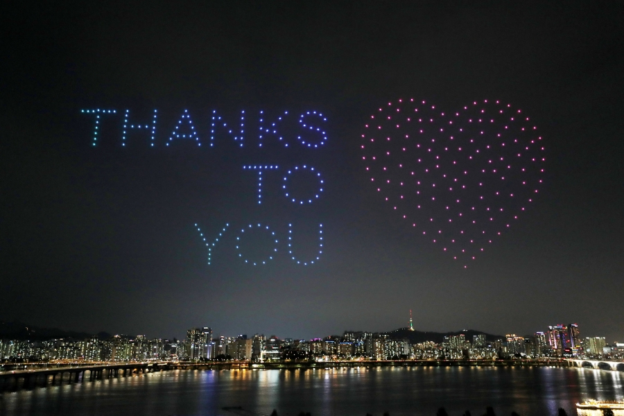 The words Thanks to you are drawn in the sky over a city by lights on drones.