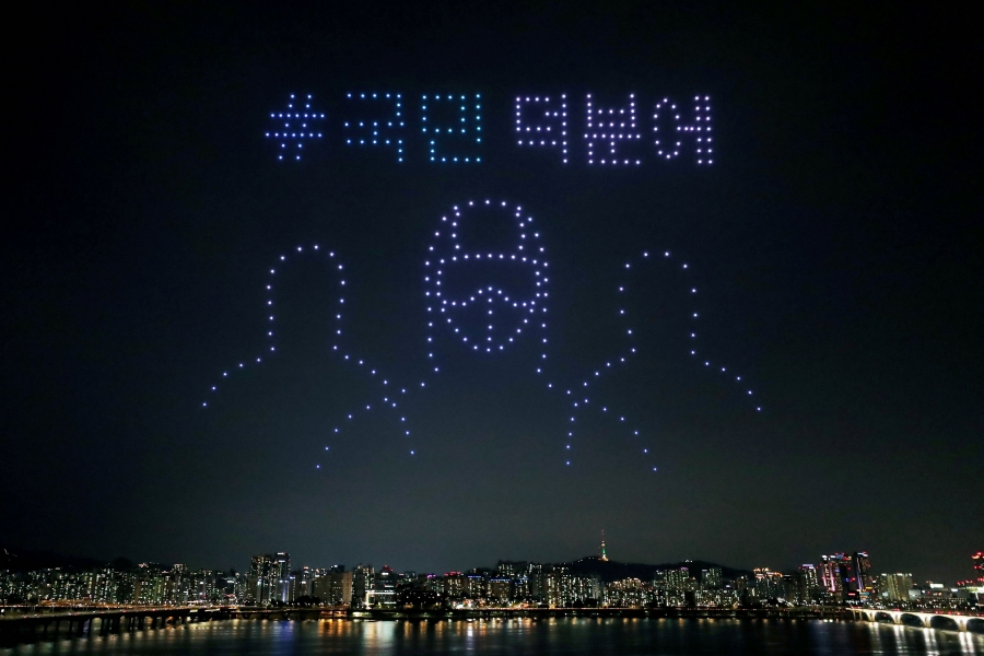 Drones fly over the sky of Seoul creating the image of medical workers in protection gear.