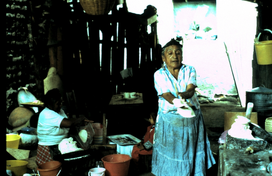A woman stands up while molding tamales with her hands.