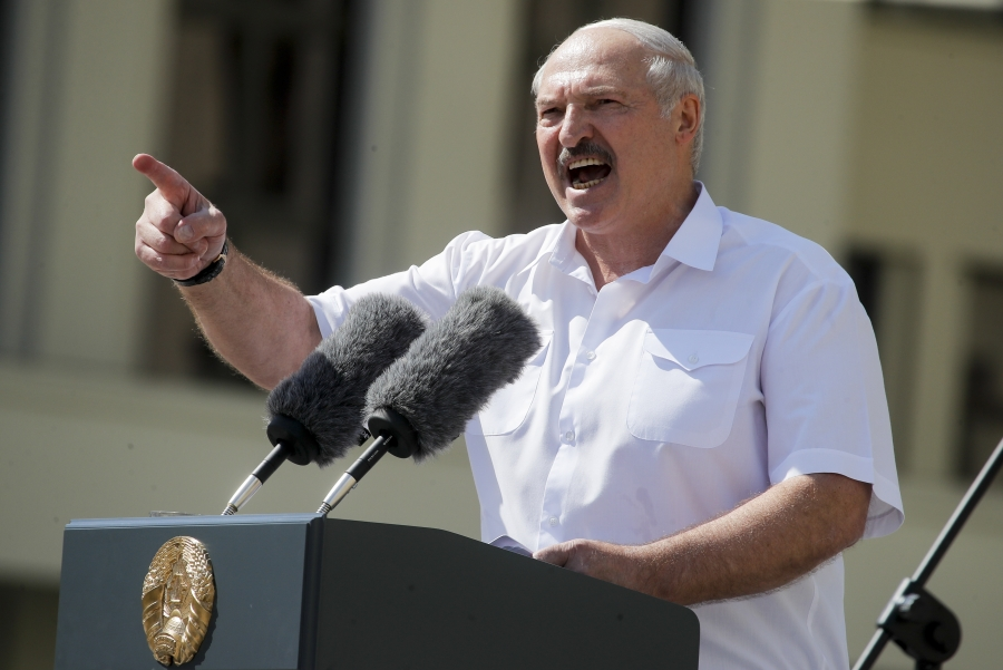 Alexander Lukashenko passionately speaks into a microphone, with his hand up and finger waving at the audience.