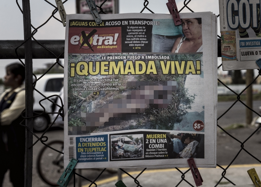 The front page of a newspaper displayed on a fence.