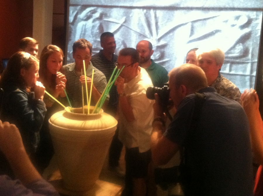 A group of people drink beer with straws out of a large vase.
