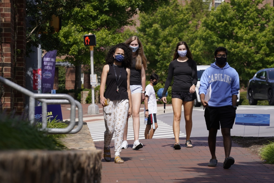 College students walking, wearing masks.