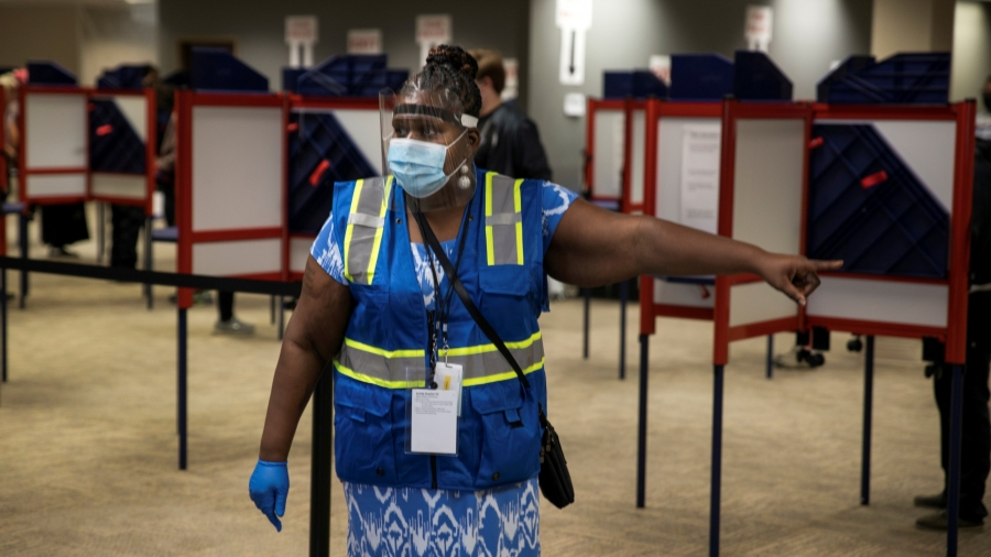 A poll worker directs voters to cast their ballots for the upcoming presidential election as early voting begins in Cincinnati, Ohio, Oct. 6, 2020.