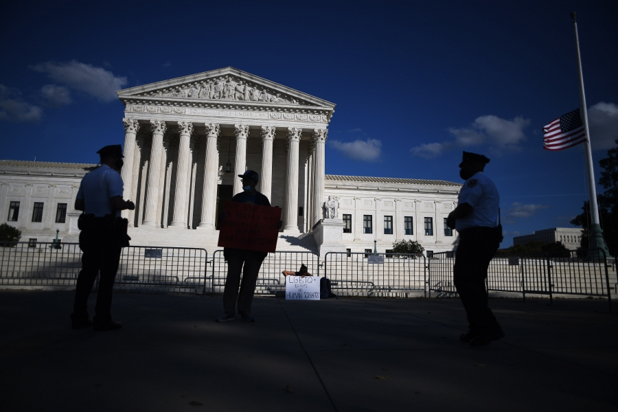 Police officers talk to one of two demonstrators who gather outside the Supreme Court in Washington, D.C., October 15, 2020, to protest the nomination of Justice Amy Coney Barrett.