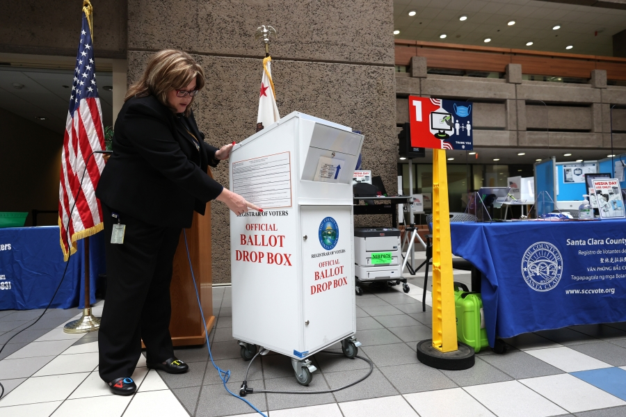 A woman stands next to a ballot box, pointing at specific details.