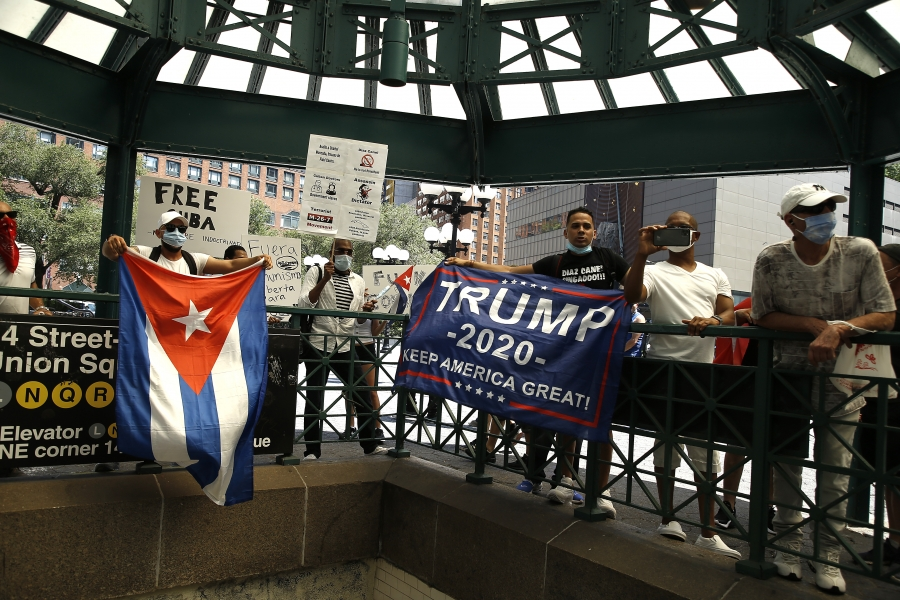 A row of Cuban Americans holding up pro-Trump flags.