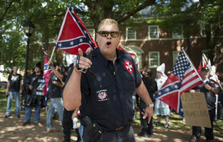 A white supremacist cheers with a crowd.