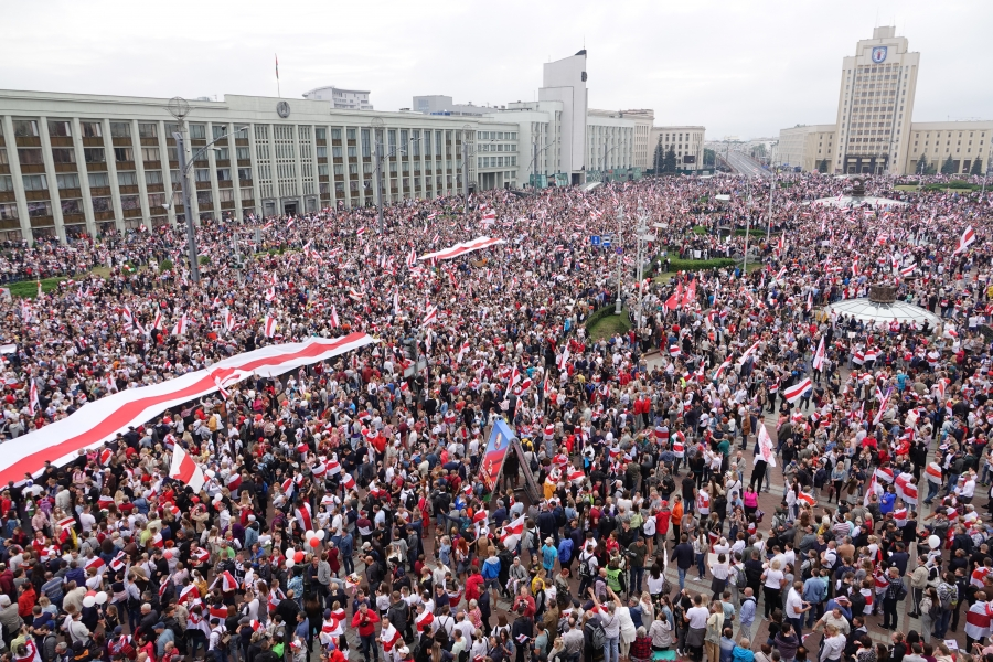 A massive crowd of people gather for a protest in the Belarusian capital. The nation's flag colors, red and white, are apparent throughout the photo.