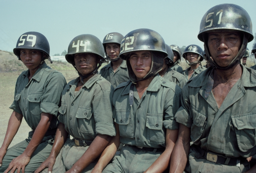Four women dressed in Army green and helmets sit side by side and make eye contact with the camera.