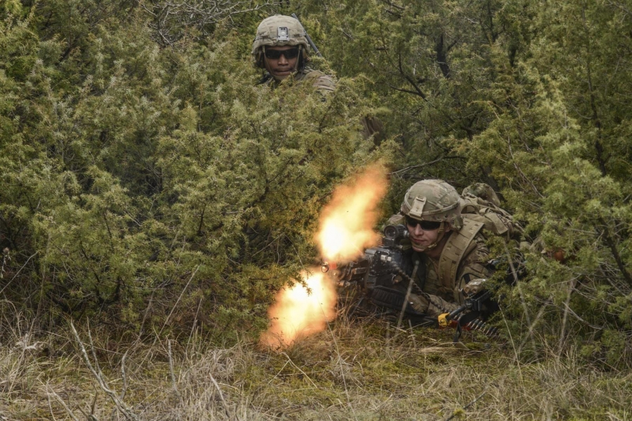 Two soldiers hunch down in a bush. The photo displays the bullets from one of the guns mid-fire.