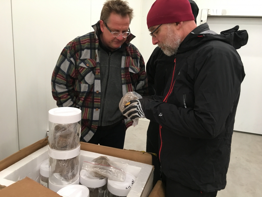 Geomorphologist Paul Bierman (right) and geochemist Joerg Schaefer of Columbia University examine the jars holding Camp Century sediment for the first time. They were in a Danish freezer set at -17 F.