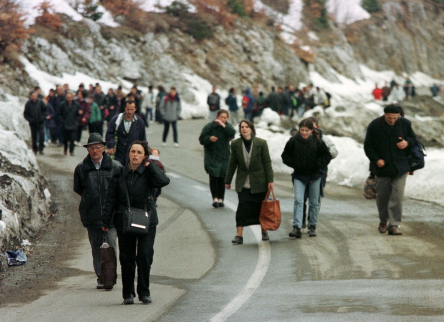 A large group of people walking on a mountainside road.