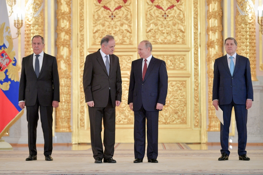 Four men stand in a line – the two in the middle at Montenegro's ambassador to Russia and Vladimir Putin