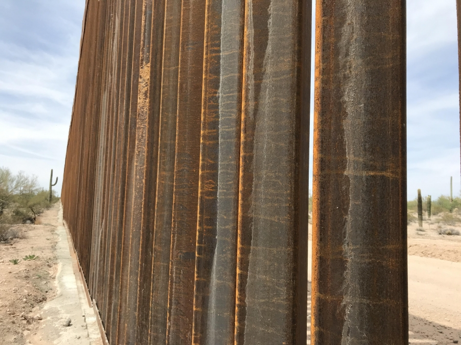A view from the Mexican side of a 30-foot border wall, peeking through the slabs to show the US side of the border.