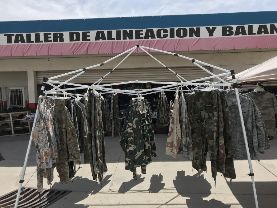 Racks of camouflage clothing outside a tire alignment shop