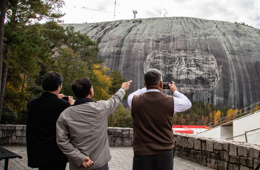 Tourists point at and take cell phone photos of Stone Mountain.