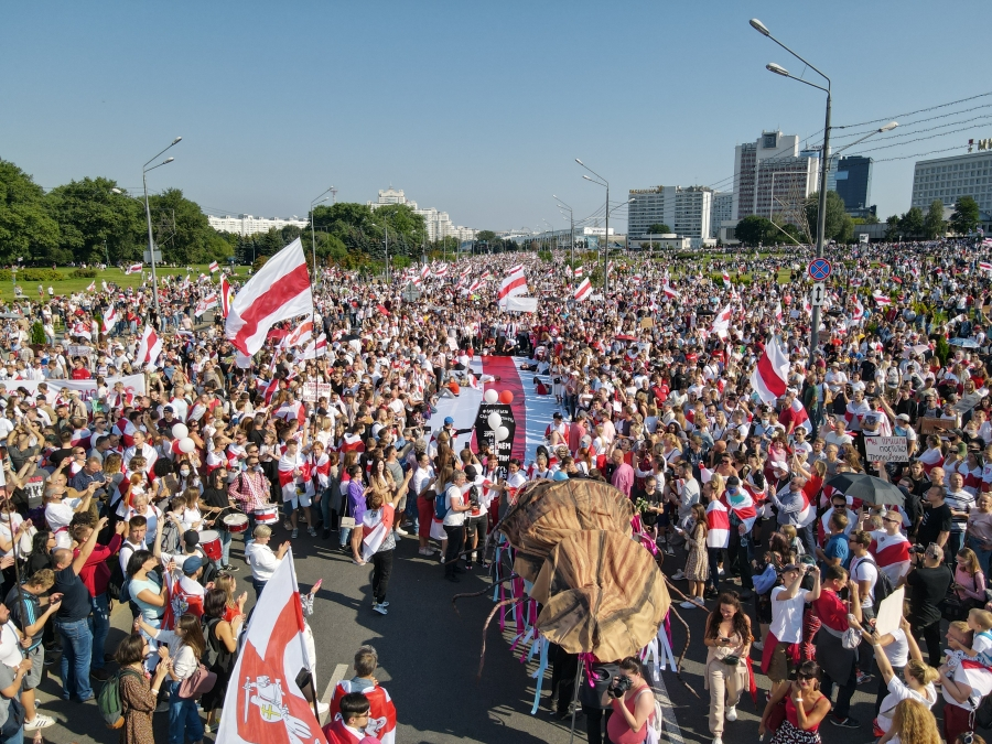 A crowd of people, many of whom are holding Belarus's national flag..