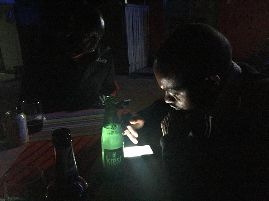 Two Maasai men check their phones at a local bar.