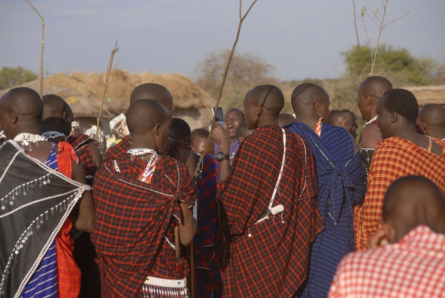 A young Maasai man checks his phone during a ceremonial dance.