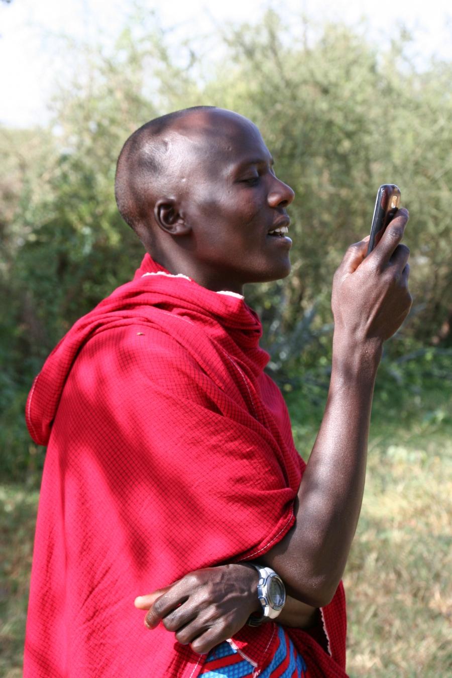 A Maasai man checks the number of an incoming call.