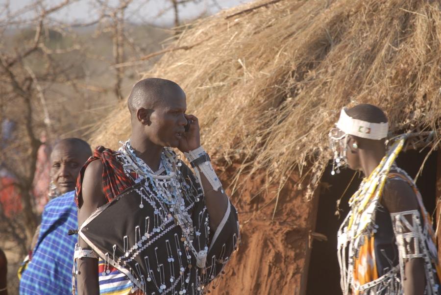 A Maasai man talks on his phone during a community gathering.