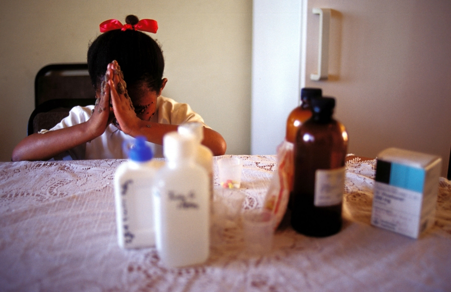 A young girl folds her hands in prayer in front of her. Out of focus, in front of her, is a group of medication bottles.