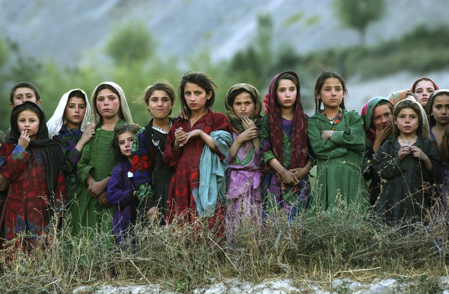 Local girls look at UNworkers unloading ballot kits from a UNhelicopter in Ghumaipayan Mahnow village, some 256 miles)northeast of Kabul, Afghanistan, on Oct. 4, 2004. By air wasthe only way to deliver the electoral material in the inaccessible areas o