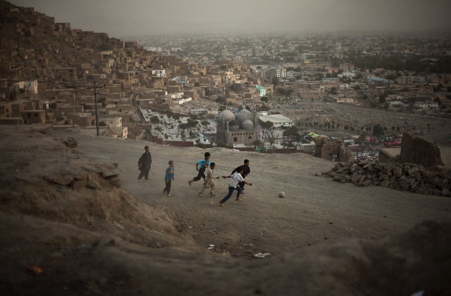 Afghan children play football in a street in Kabul, Afghanistan, onJuly 17, 2009.