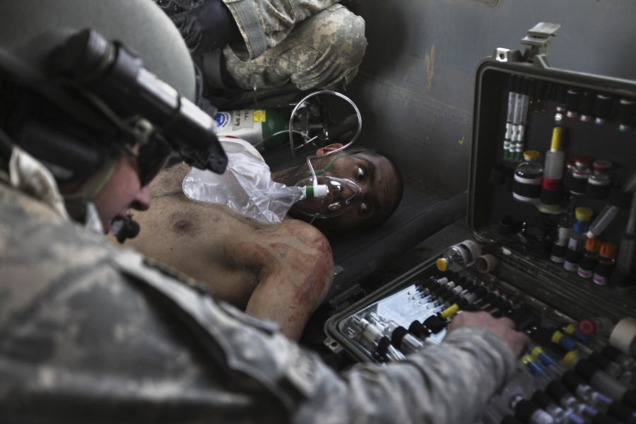 Airborne in a USArmy Task Force Pegasus helicopter, USArmy Staff Sgt. and flight medic Robert B. Cowdrey, of La Junta, Colo., gives medical care to an Afghan National Army soldier with a gunshot wound, during a medevac mission over Marjah, Helmand provi
