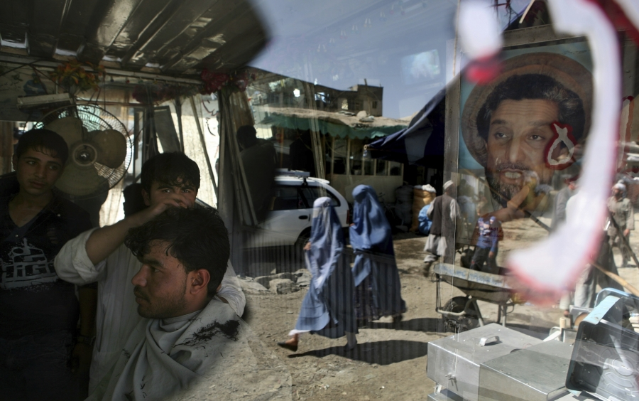 An Afghan barber works on a customer in his shop as a portrait of Afghanistan national hero Ahmad Shah Massoud adorns its door in Kabul, Afghanistan, on Sept. 29, 2009.