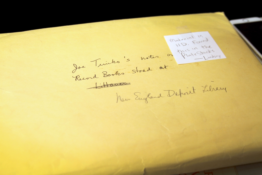 "A yellow manila envelope has a Post-it it that says ""Found this in the plate stacks - Lindsay"" and the name a library crossed out and replaced with ""New England Deposit Library."""