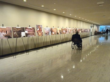 John Hockenberry, host of PRI's The Takeaway, visits the exhibit of Ceasar's photos at UN headquarters in New York.