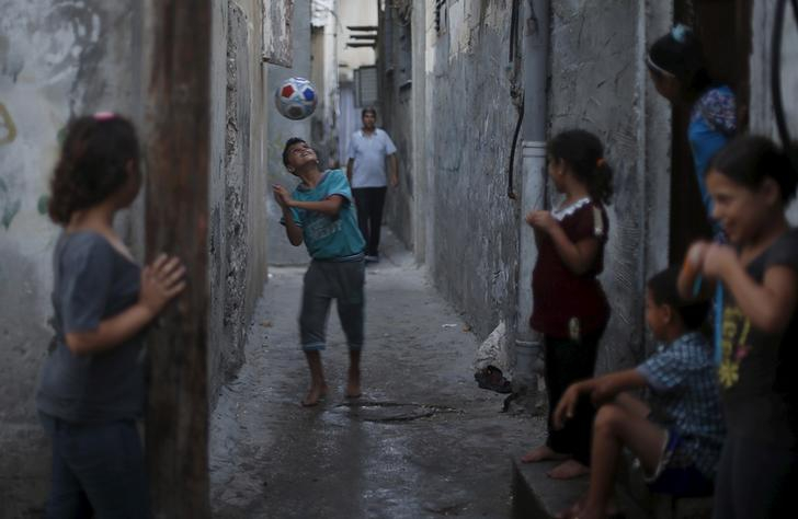 A boy smiles as he bounces a soccer ball off his head at a refugee camp in Gaza City. Several children watch.