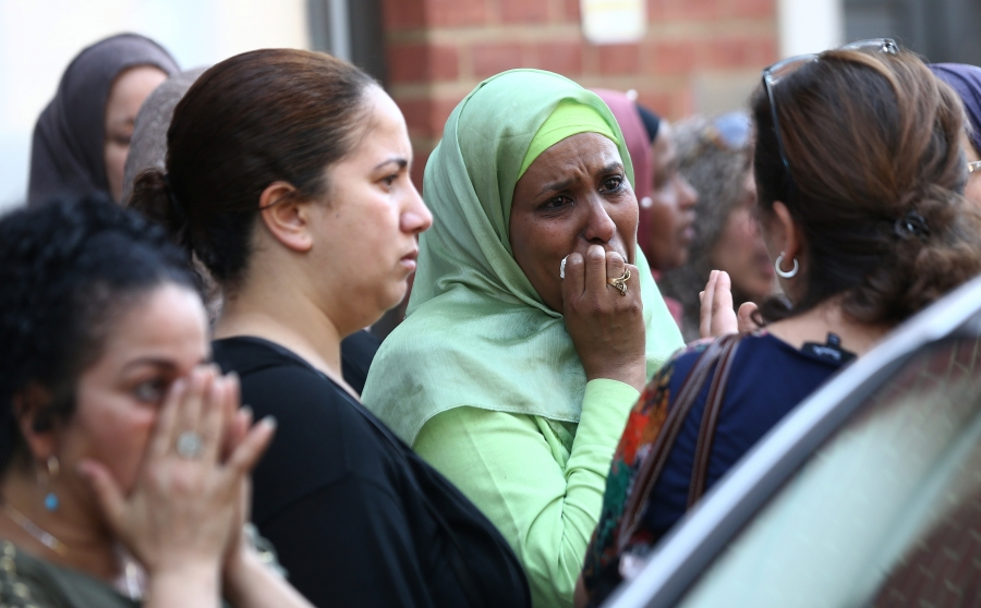People react near a tower block severely damaged by a serious fire, in north Kensington