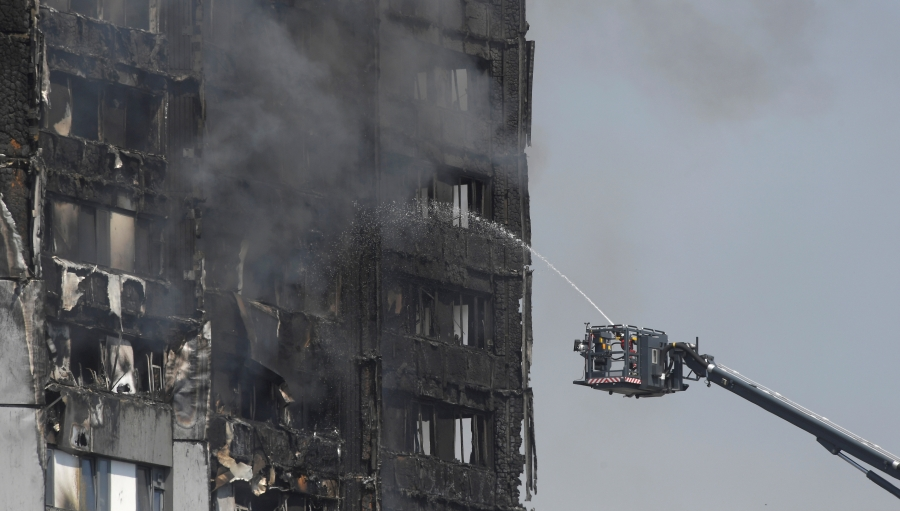 Firefighters direct jets of water onto a tower block severely damaged by a serious fire
