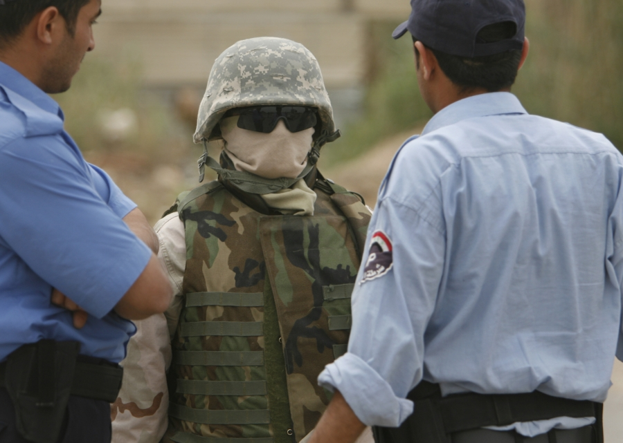 A masked interpreter talks with Iraqi policemen in Mahmudiya, south of Baghdad, April 25, 2007. Iraqi interpreters, fearing reprisal for working with US forces, sometimes wore masks to protect their identies.