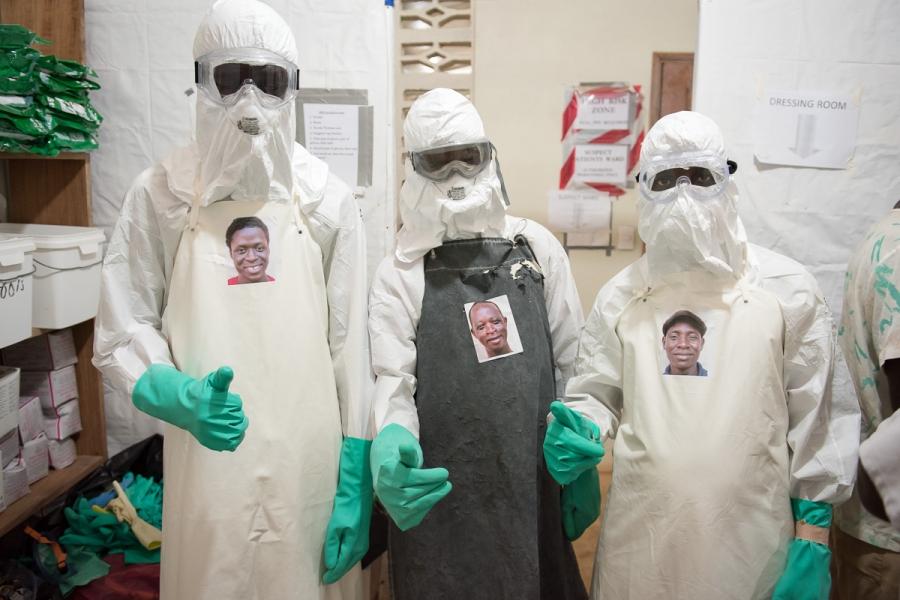 Health workers Morris Zolu, Kaifouba Kamara, and Joseph Walatee wearing their portraits.