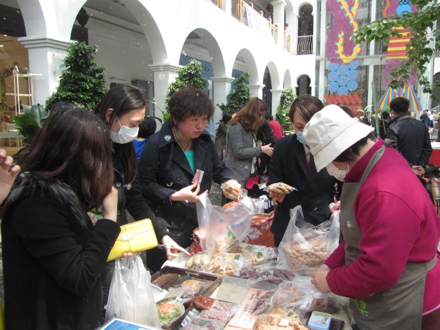 Customers peruse the offerings at the vegan bakery table at a Beijing farmers' market.