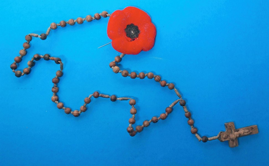 Rosary beads and a poppy found in the underground chamber.