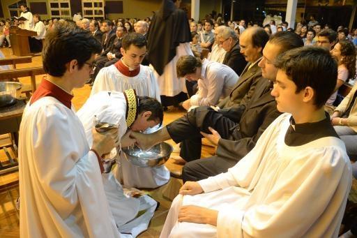 Father Carlos Urrutigoity kisses the foot of a congregant in Ciudad Del Este.