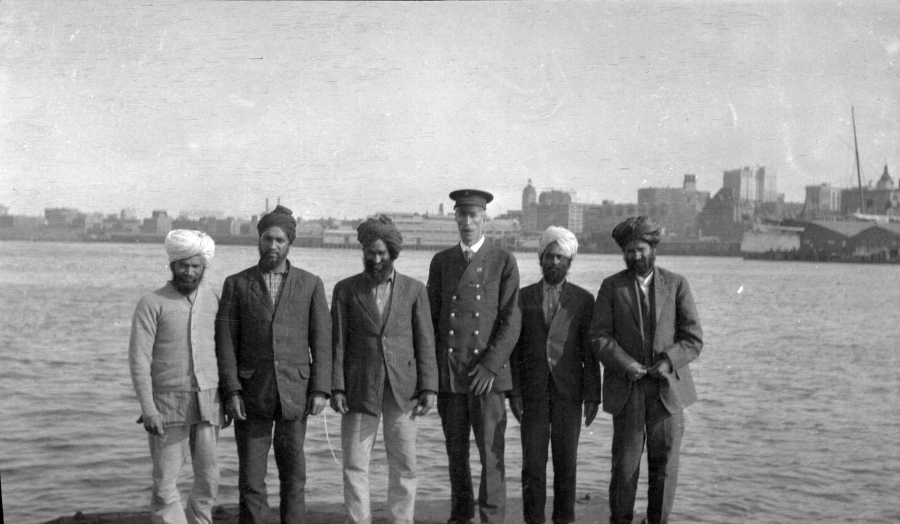 Passengers aboard the Komagata Maru in Vancouver harbor, with photographer James L.Quiney (in uniform)