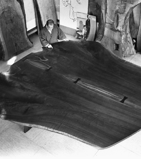 """George Nakashima examines his third """"peace altar."""" It's a table constructed with two giant cuts of black walnut attached together with butterfly joints."""