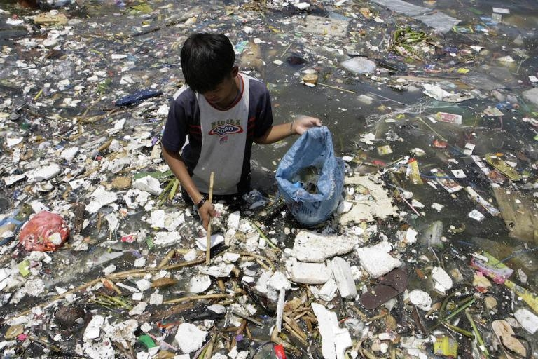 A boy collects plastic near a polluted coastline to sell in Manila, April 9, 2008.